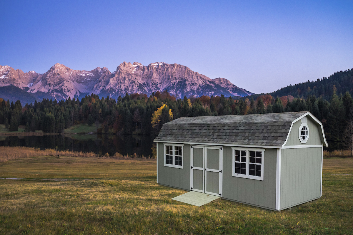 Portable lofted garden shed with shingle roof, mountains in background, Countryside Barns, Portable Building Manufacturer