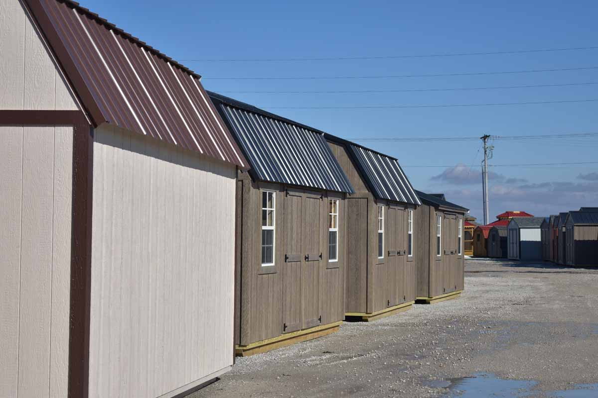 Line up of lofted garden shed with driftwood urethane and black metal roof